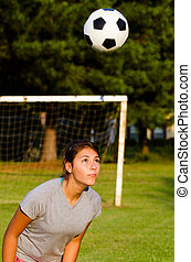 Teen girl heading soccer ball while playing on field