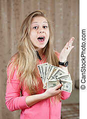 Happy woman shows bundles of US dollars - Happy young woman...