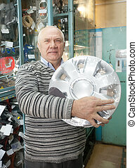man buys  automotive wheel cover