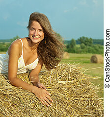 girl laying on straw bail - Young girl laying on top of...