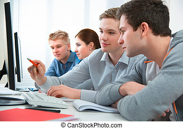 students attending training course in a computer classroom -...