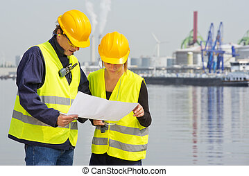 Discussing blueprints - Two engineers, wearing safety gear,...