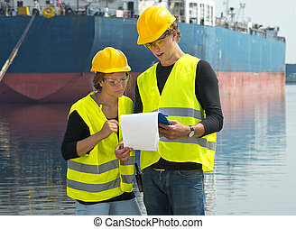 Dockers checking freight papers - Two dockers checking the...
