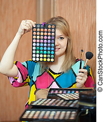 Female visagiste with cosmetics ready for job
