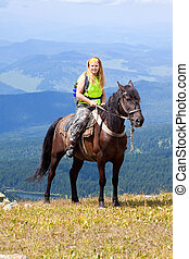 Horseback riding - Female rider on horseback at mountains...