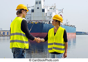 Docker handshake - Female docker shaking hands with a male...