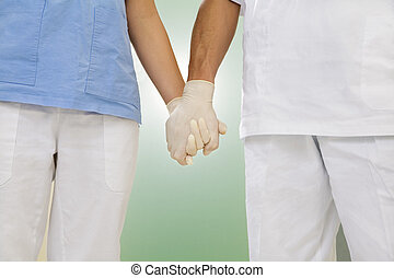 dentist - doctor and nurse holding hands in the hospital