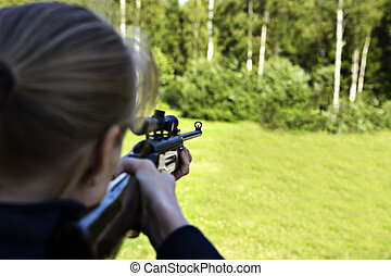 Woman targeting with hand weapon through sight - Woman...
