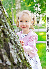 Portrait of a little lovely girl playing in the park