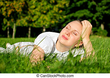 Young woman relaxing on the grass in park