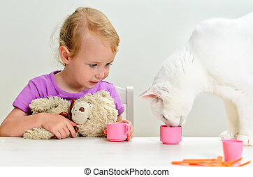 Cute little girl and cat playing with plastic dishes