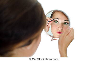 Young attractive woman plucking her eyebrows with tweezers...