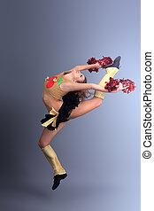 acrobatics - Beautiful girl cheerleader posing at studio.