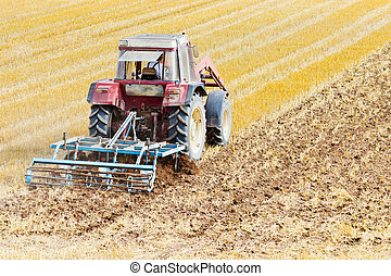 Tractor with cultivator - A tractor with a cultivator on a...