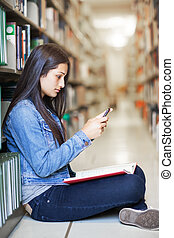 Hispanic student texting - A shot of an Hispanic student...