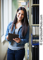 Hispanic college student using tablet PC - A portrait of an...