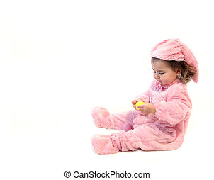Baby Bunting - Baby girl hold a yellow Easter egg and tries...