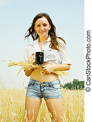 Girl with beer and wheat ear at cereals field