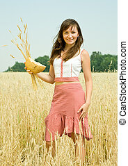 Young girl with bread at cereals field in summer