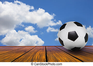soccer football on wood terrace with blue sky white cloud