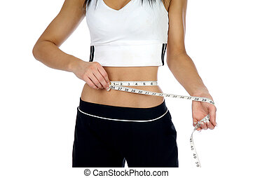Young woman measuring her waist with a tape measure