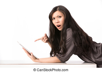 Shocked woman pointing at her digital-tablet. - Portrait of...