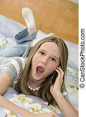 Preteen - Caucasian preteen girl laying in bed talking on a...
