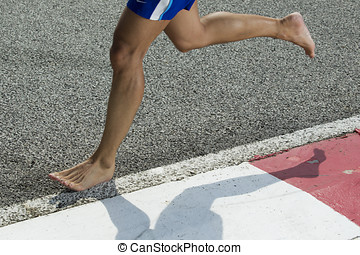 Closeup of a runners feet barefoot running - A closeup of a...