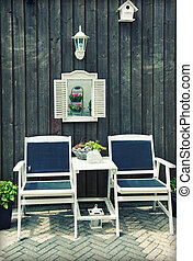 wooden chairs by home garden - flowers and seasonal plants...
