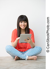 Young Asian girl sitting holding a Digital Tablet. - Pretty...