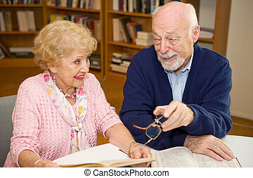 Seniors Meet in Library - Senior man and woman meeting at...