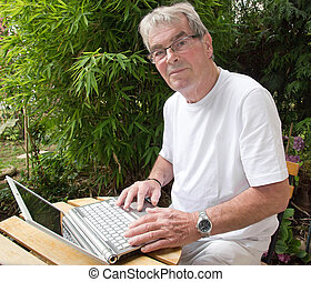 Active retired person and modern, using a laptop computer