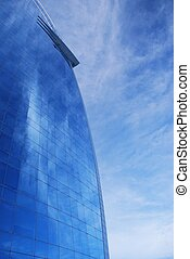 Glass facade reflecting a dramatic blue sky