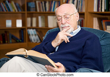 Interesting Reading - Closeup of senior man sitting in an...