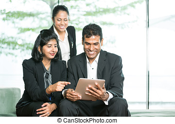 Indian Business people looking at a digital tablet.