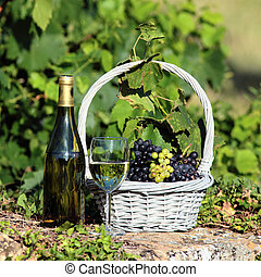 glass and bottle of wine with grapes in basket
