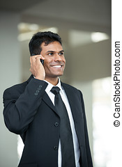 Indian business man using mobile phone - Portrait of...