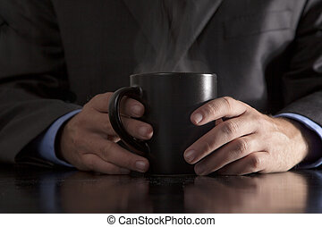 Executive Holds Steaming Coffee - A young executive holds a...