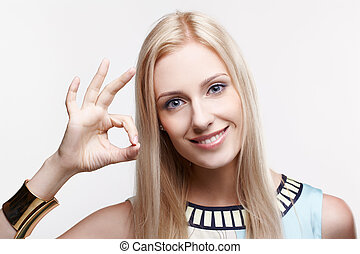ok - portrait of young beautiful blonde woman showing ok...