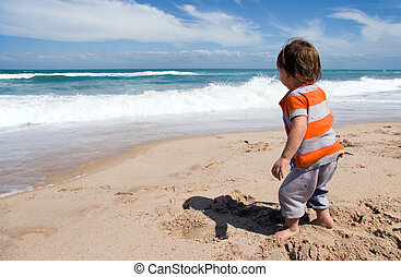 Toddler on Beach - Toddler age boy standing on sandy beach...