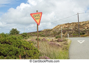 Give way sign. - A rural road junction with a sign on a post...