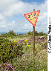 Give way sign. - A sign on a post with the words 'GIVE WAY'...