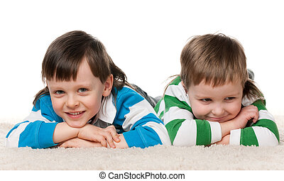 Two boys lie on the carpet
