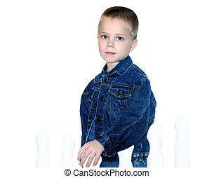 Boyish Charm - Handsome little boy stands in the corner of a...
