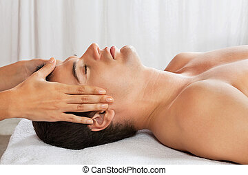 Man Receiving Head Massage At Spa - Side view of young man...