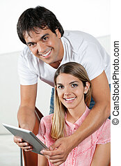Happy Couple With Tablet PC - Portrait of happy young man...