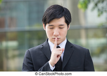 Business man with his finger on his lips going shh - Asian...