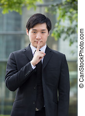 Business man with his finger on his lips going shh. - Asian...