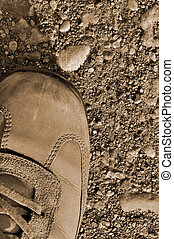 Hiking boot off-road shoe on hard arid dried soil in sepia,...