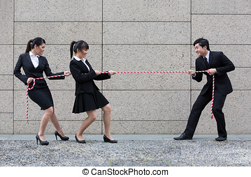Business people having a tug of war fight. - Two Asian...
